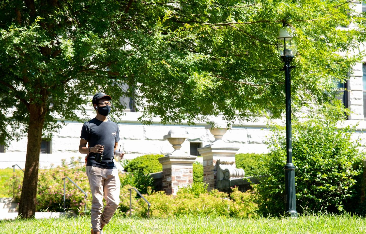 Student wearing a mask walks across the Princeton campus